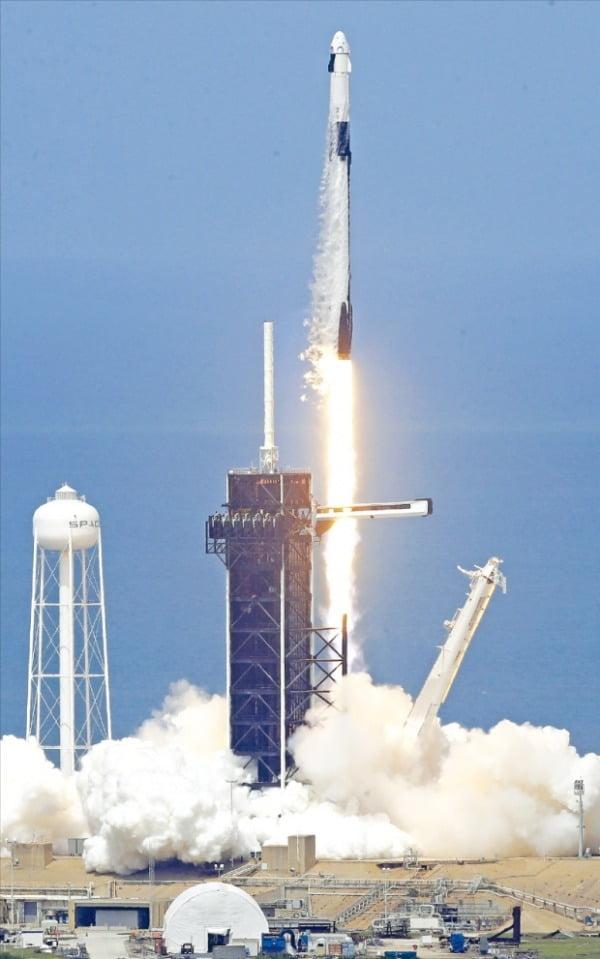 스페이스X의 팰컨9 로켓에 실린 유인 우주선 크루드래건이 지난달 30일 미국 플로리다주 케이프커내버럴 케네디우주센터에서 하늘로 솟구치고 있다. 민간 기업의 유인 우주선 발사가 성공하면서 화성 탐사 등 민간 우주개발 사업이 본격화할 것으로 기대를 모으고 있다.  AP연합뉴스