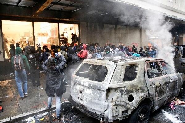 미국 시애틀에서 30일(현지시간) 흑인 조지 플로이드가 경찰의 가혹행위로 사망한 사건에 항의하는 시위가 벌어져 경찰 차량이 불에 탄 가운데 군중들이 인근의 노드스트롬 매장을 약탈하고 있다/사진=연합뉴스