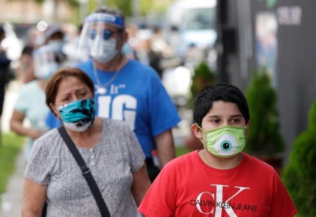 미국 플로리다주의 주민들이 마스크를 착용하고 거리를 지나가고 있다./사진=AP