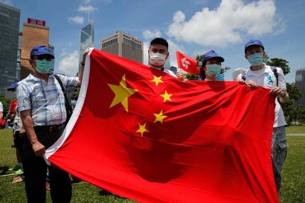 중국 중앙정부를 지지하는 홍콩 시민들이 30일 전인대 상무위원회의 홍콩 국가보안법 통과를 환영하는 뜻에서 중국과 홍콩 국기를 들어보이고 있다.  AP연합뉴스