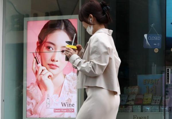 서울 명동의 문 닫은 화장품 가게 앞을 한 시민이 답답함에 마스크를 턱에 걸쳐둔 채 지나가고 있다. 사진=뉴스1
