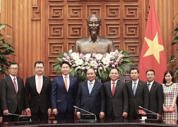 최태원 SK그룹 회장(왼쪽 세번째)과 최재원 SK그룹 수석부회장(두번째)이 지난해 6월 응웬 쑤언 푹 베트남 총리 공관을 방문해 기념 사진을 찍고 있다. SK제공