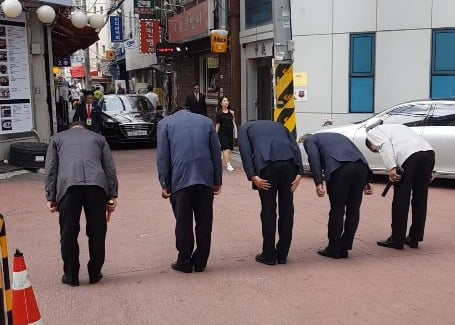 허경영 대표 경호원들이 허경영 대표 차량을 향해 인사하고 있는 모습.