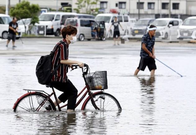 한 학생이 불어난 빗물을 가르며 자전거를 타는 모습 [사진=AP 연합뉴스]