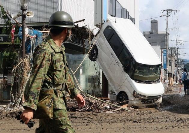 일본 자위대원이 망가진 자동차를 바라보며 지나가고 있다. [사진=EPA 연합뉴스]