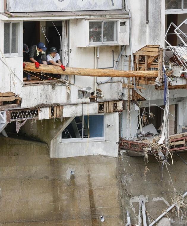 커다란 목재가 빗물에 떠내려와 집을 덮쳤다. [사진=AP 연합뉴스]