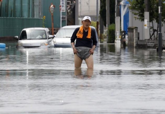 노인이 홍수로 불어난 길을 걷고 있다 [사진=EPA 연합뉴스]