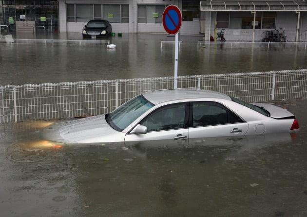 헤드라이트가 켜진 채 빗물에 잠긴 자동차 [사진=EPA 연합뉴스]