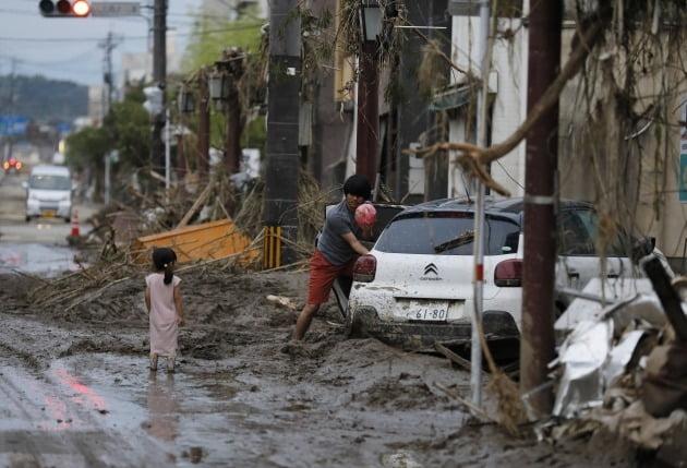 어린 아이와 보호자가 진흙으로 뒤덮힌 차량에서 물건을 꺼내는 모습 [사진=EPA 연합뉴스]