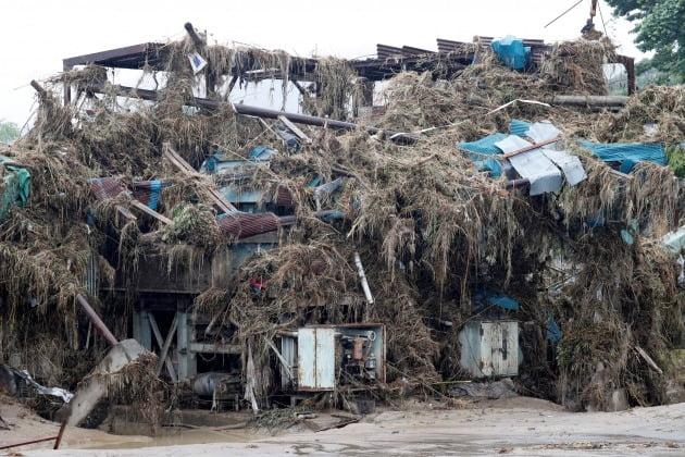 구조물을 뒤덮은 나무와 토사물, 쓰레기 더미 [사진=로이터 연합뉴스]