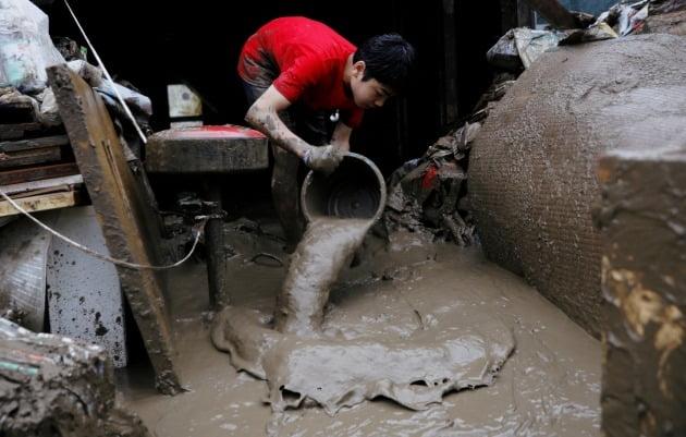 현지의 한 어린이가 집 안으로 쏟아진 진흙을 양동이로 퍼내고 있다. [사진=로이터 연합뉴스]