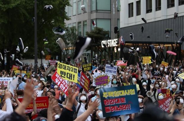 정부의 부동산 규제와 세금인상 등에 발반한 시민들이 25일 저녁 서울 중구 을지로 예금보험공사 앞에서 촛불집회를 열었다. 시위 참가자들이 신발을 던지는 퍼포먼스를 진행하고 있다. (자료 한경DB)
