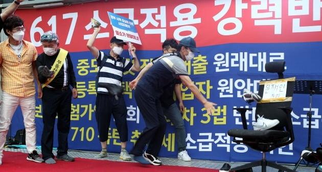 25일 서울 다동 예금보험공사 앞에서 열린 부동산 정책 규탄 촛불집회에 참가한 시민들이 문재인 대통령의 이름이 적힌 의자에 신발을 던지는 퍼포먼스를 하고 있다. /뉴스1