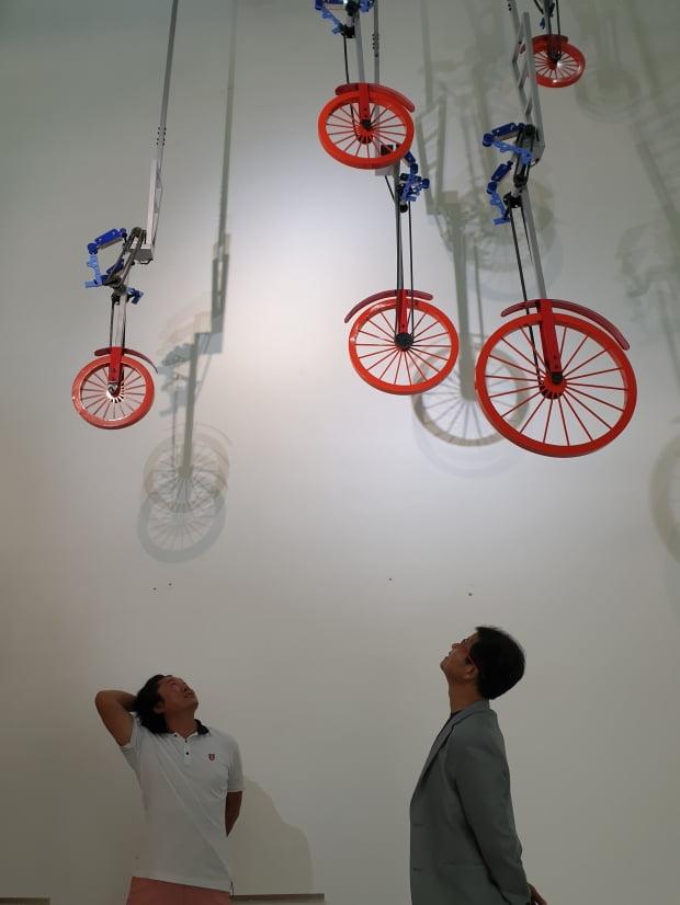3층 높이의 천장에 매달린 손봉채 작가의 키네틱 아트 '시간여행'을 박헌택 영무파라드호텔 대표(오른쪽)와 손 작가가 올려다 보고 있다.