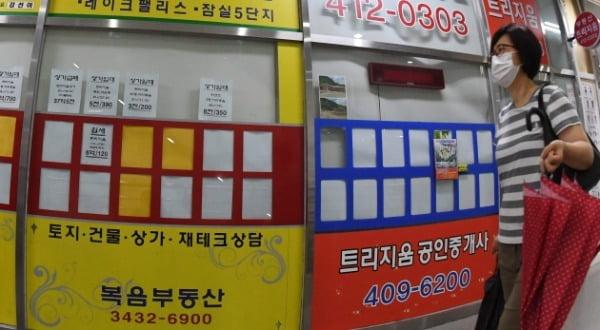 지난 29일 한 시민이 서울 송파구 잠실의 한 공인중개사무실 앞을 지나가고 있다. /사진=신경훈 기자 khshin@hankyung.com