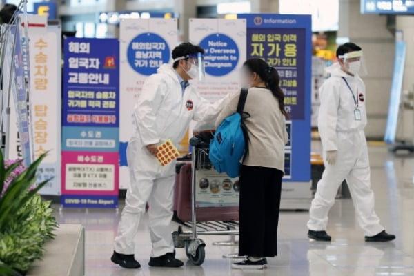지난 29일 인천국제공항 제1여객터미널 입국장에서 해외 체류 후 입국한 승객이 의료진을 비롯한 공항직원들과 문답을 나누고 있다. /사진=뉴스1