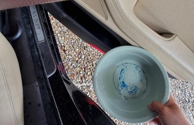 사진은 조립 불량 주장이 제기된 제네시스 G80 2세대 부분변경 모델에 차오른 물을 차주가 퍼내고 있는 모습. 사진=보배드림 캡쳐