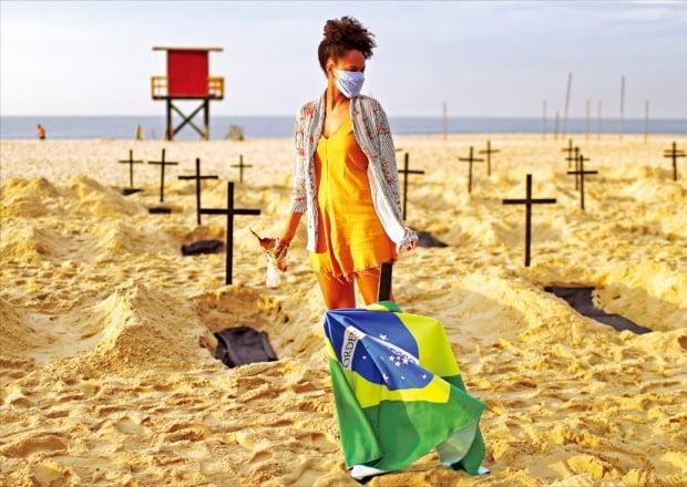 < 코로나 대응 실패…브라질 해변서 항의 퍼포먼스 > 브라질의 한 인권운동단체가 코로나19 대응에 실패한 정부에 항의하기 위해 리우데자네이루 해변에 11일(현지시간) 모조 무덤 100개를 세웠다. 한 여성이 브라질 국기가 걸린 무덤 사이를 걷고 있다.   /로이터연합뉴스