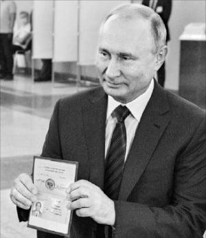 블라디미르 푸틴 러시아 대통령이 지난 1일 투표소에서 여권을 보여주고 있다.  /EPA연합뉴스