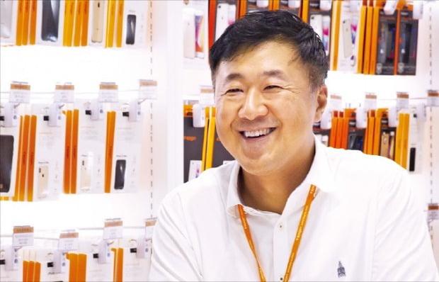 김대영 슈피겐코리아 대표가 자사의 휴대폰 케이스를 소개하며 환하게 웃고 있다.   /슈피겐코리아 제공