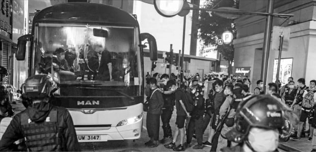 < 홍콩보안법 시행 첫날 370명 체포 > 홍콩 반환 23주년 기념일이자 홍콩 국가보안법이 시행된 지난 1일 홍콩보안법에 반대하는 시위에 참여했다가 체포된 시민들이 경찰 버스에 오르고 있다.   /AFP연합뉴스