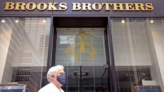 """< 파산 신청한 브룩스브라더스 > 202년 역사의 미국 의류 브랜드 브룩스브라더스가 8일(현지시간) 법원에 파산 보호신청을 했다. 회사 측은 """"코로나19가 경영에 막대한 피해를 초래했다""""고 밝혔다. 한 행인이 뉴욕 맨해튼의 브룩스브라더스 매장 앞을 지나가고 있다.  /신화연합뉴스"""