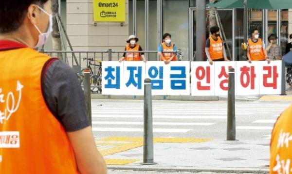 민주노총 조합원들이 10일 정부세종청사 앞에서 최저임금 인상을 요구하고 있다.  연합뉴스