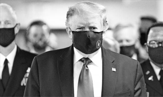 도널드 트럼프 미국 대통령(가운데)이 11일(현지시간) 마스크를 쓰고 메릴랜드주 월터리드 국립군의료센터를 둘러보고 있다. 트럼프 대통령이 공개 행사에서 마스크를 쓴 채 등장한 건 이번이 처음이다.  UPI연합뉴스