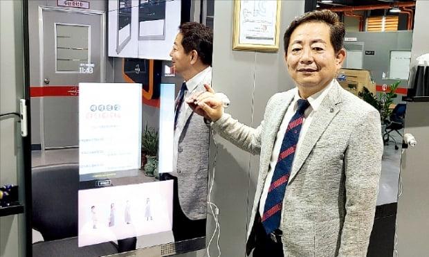 안덕근 엘리비젼 대표가 미용실용 스마트 미러 '미라보'를 통한 광고를 시연하고 있다.  김동현 기자