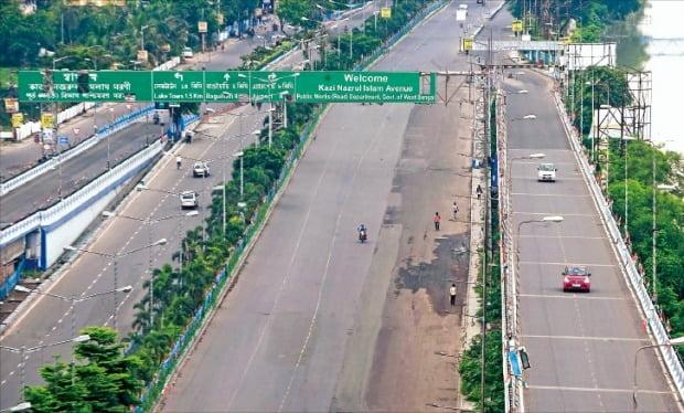 < 경제재개 너무 성급했나…인도, 다시 봉쇄령 > 자동차와 행인들이 지난 25일 인도 콜카타주의 한산한 도로를 지나고 있다. 콜카타주는 코로나19 재확산을 막기 위해 24일부터 2주간 봉쇄령을 내렸다.  AFP연합뉴스
