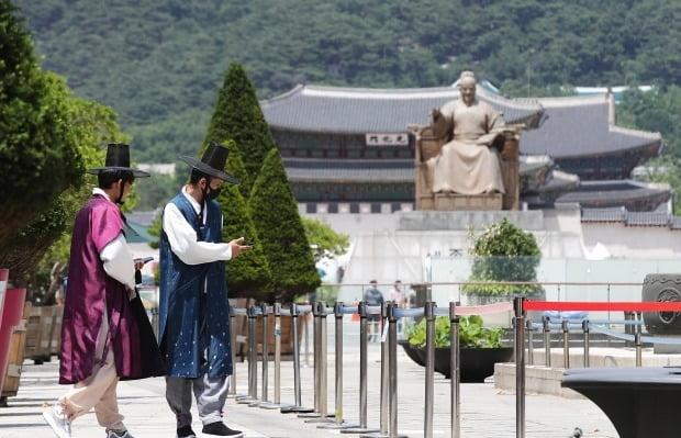 서울 광화문 광장을 찾은 외국인 관광객이 한복 차림에 마스크를 쓰고 걷고 있다. 사진=연합뉴스