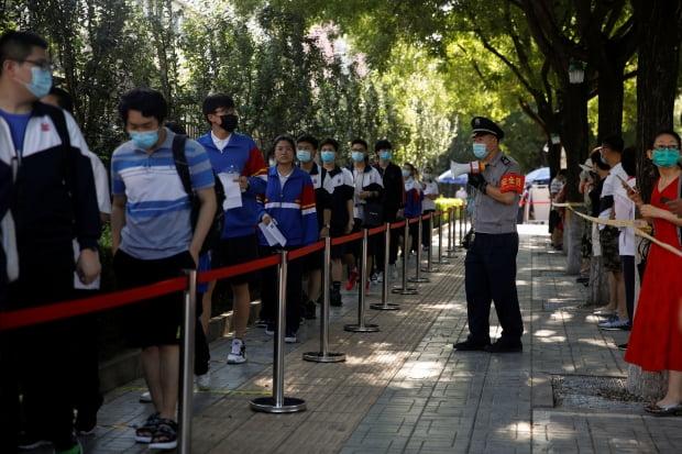 중국 대입 수험생들이 7일 '가오카오'(高考ㆍ대학 입학시험)를 치르기 위해 마스크를 쓰고 고사장인 베이징의 한 고교에 줄지어 들어가고 있다. 신종 코로나바이러스 감염증(코로나19) 여파로 한달간 연기됐던 가오카오는 이날부터 중국 전역에서 개시됐다. 사진=연합뉴스