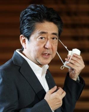 마스크를 벗는 아베 신조 일본 총리. / 사진=EPA