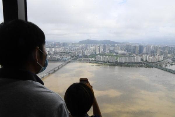 한강에 홍수주의보가 발령된 6일 서울 63빌딩에서 시민들이 한강을 내려다보고 있다. /사진=강은구 기자 egkang@hankyung.com