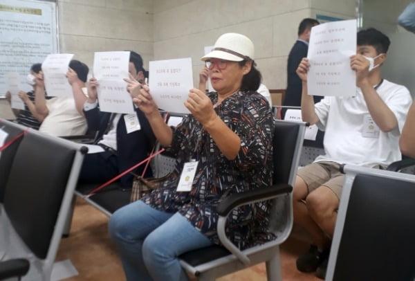 지난달 16일 열린 전북 김제시의회 본회의장에서 시민들이 부적절한 관계로 물의를 빚은 의원들에 대한 제명을 요구하는 글을 들고 있다. /사진=연합뉴스