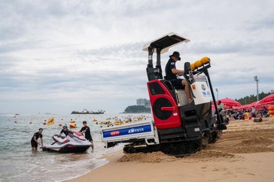 119 구조대원들이 속초해수욕장에서 동양물산기업이 기증한 다목적 운반차를 이용해 인명구조용 제트스키를 옮기고 있다.  /동양물산 제공