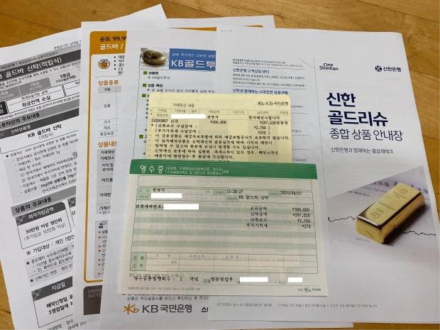 지난 7일 KB은행에서 가입한 골드바 신탁 통장과 영수증 및 시중 은행 금 관련 상품 안내장. (사진=전명석 인턴기자)