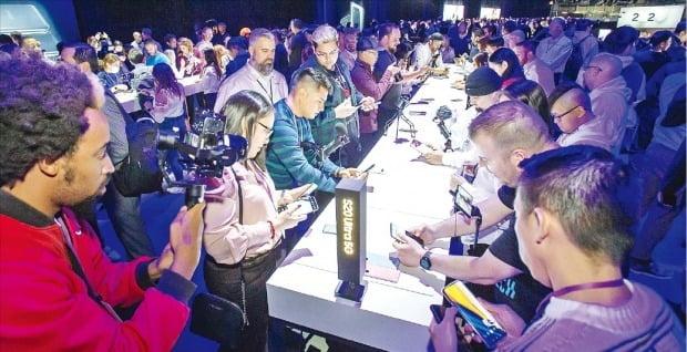 """< """"갤럭시S20 대단하네"""" > 11일(현지시간) 미국 샌프란시스코에서 열린 '삼성 갤럭시 언팩 2020'을 찾은 소비자들이 삼성전자가 새로 선보인 갤럭시S20 시리즈를 체험해보고 있다.  삼성전자 제공"""