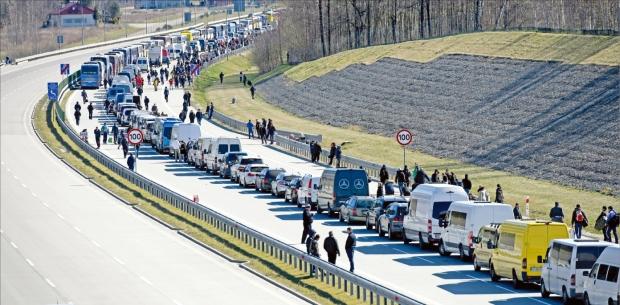 < 폴란드 입국 통제로 국경 '장사진' > 15일(현지시간) 우크라이나와 국경을 접한 폴란드 남동부의 코르초와에서 입국 통제로 도로에 차들이 멈춰 서 있다. 폴란드 정부는 코로나19 확산을 막기 위해 이날부터 외국인의 입국을 금지했다.  EPA연합뉴스