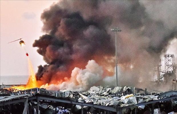 4일(현지시간) 레바논 수도 베이루트 항구 인근 폭발 현장에서 화재 진압을 위해 긴급 동원된 헬기가 불을 끄고 있다. 이날 대형 폭발로 인한 열과 충격으로 일대 건물이 무너졌다.   /AFP연합뉴스