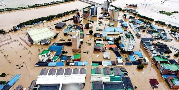 < 섬진강 범람…물에 잠긴 구례군 > 지난 주말(7~8일) 동안 380㎜의 집중 호우가 쏟아진 전남 구례군에선 섬진강과 서시천이 범람해 1100여 가구가 침수되는 등 막대한 피해가 발생했다. 9일 구례읍 일대가 자동차와 주택 지붕만 간신히 보일 정도로 물에 잠겨 있다.  /뉴스1