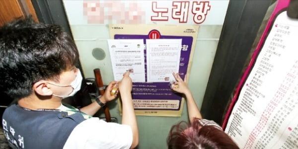 < 노래방 집합금지명령 > PC방 노래방 등을 운영하는 자영업자들이 코로나19 사태를 견디지 못해 가게를 매물로 내놓는 사례가 늘고 있다. 서울 성동구 문화체육과 직원들이 20일 한 노래방에 집합금지 명령서를 붙이고 있다.  성동구  제공