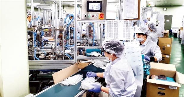 경기 시흥에 있는 한 마스크 생산 공장에서 직원들이 마스크 품질 검사를 하고 있다.