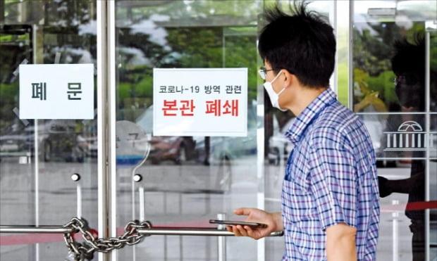 국회 출입기자가 신종 코로나바이러스 감염증(코로나19) 확진 판정을 받아 국회가 27일 폐쇄됐다. 한 시민이 자물쇠가 걸린 국회 본관 출입구 앞을 지나가고 있다.  /신경훈 기자 khshin@hankyung.com
