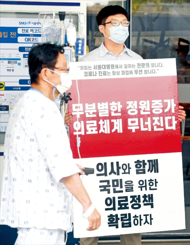 31일 서울 종로구 서울대병원 본관 앞에서 한 전문의가 정부가 추진하고 있는 의대 정원 확대, 공공의대 설립 등을 반대하며 1인 피켓 시위를 하고 있다.  허문찬기자 sweat@hankyung.com