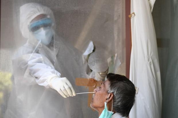 사신종 코로나바이러스 감염증(코로나19) 봉쇄 조치가 풀리면서 확진자 수가 급증하고 있는 인도 뉴델리에서 지난 16일(현지시간) 의료진이 한 남성의 검체를 채취하고 있다. 사진=연합뉴스