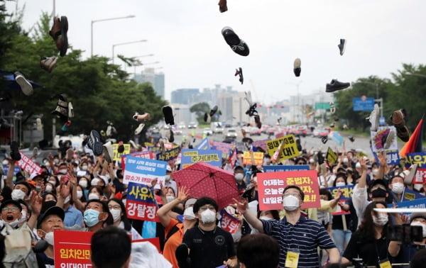 지난 1일 서울 여의도에서 임대사업자협회 추인위원회 등 부동산 관련단체 회원들이 정부의 부동산 규제에 반대하는 집회를 열고 신발투척 퍼포먼스를 하는 모습. 연합뉴스