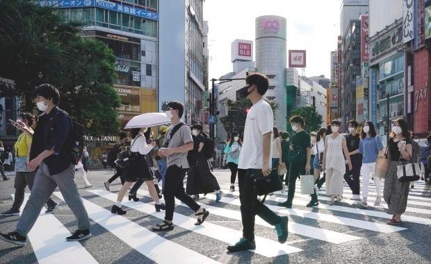 마스크를 착용한 일본 젊은이들이 도쿄 번화가인 시부야의 교차로 횡단보도를 건너가고 있다. 연합뉴스