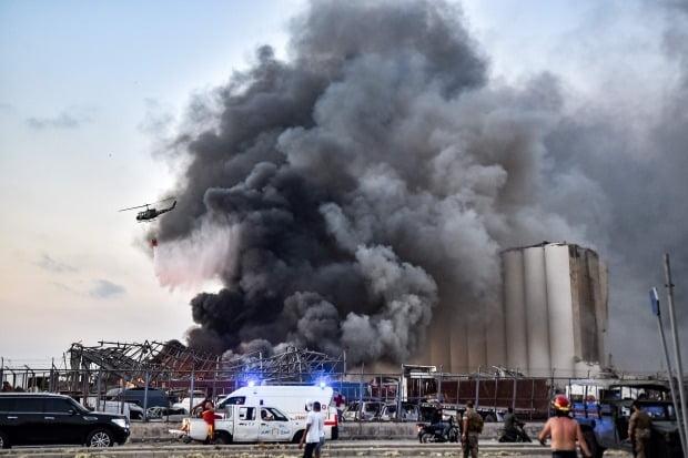4일(현지시간) 레바논 수도 베이루트 항구의 대규모 폭발 현장에서 검은 연기가 피어오르는 가운데 소방헬기가 진화 작업을 벌이고 있다. 사진=연합뉴스