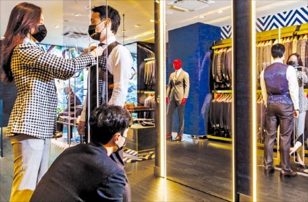 수트서플라이 전문 스타일리스트가 서울 한남 플래그십 스토어에 마련된 '세이프 스크린' 앞에서 고객에게 상품을 제안한 뒤 핏을 체크하고 있다. 삼성물산 제공